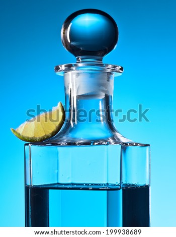 carafe with alcoholic drink and slice of lime  - stock photo