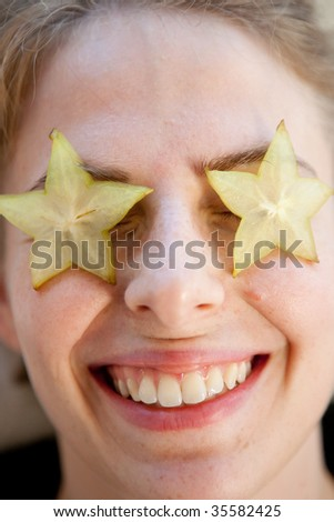 carambola fruit as star on the eyes of a young smiling woman - stock photo