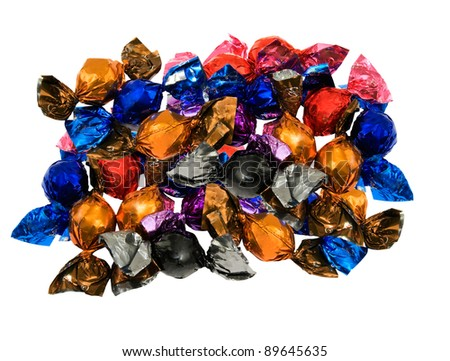 caramel and chocolate wrapped in colorful foil on a white background - stock photo