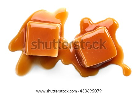 caramel candies and sauce isolated on white background, top view - stock photo