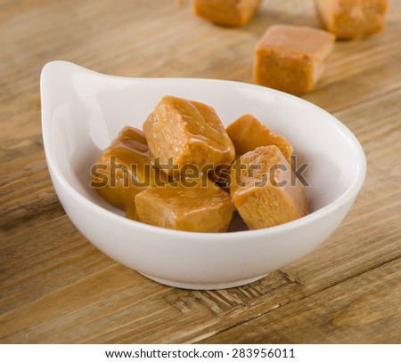 Caramel candies  on a rustic wooden table. Selective focus - stock photo