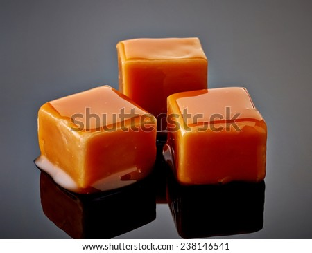 caramel candies on black background - stock photo