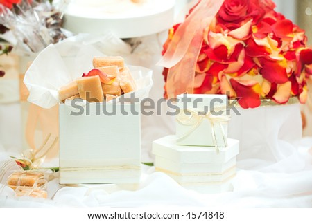 Caramel fudge confectionery and white gift boxes with ribbons as wedding guest gifts and table decorations - stock photo