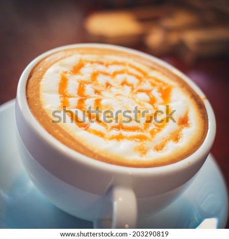 caramel hot coffee on the wooden desk - stock photo