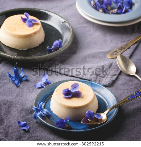 Caramel pannacotta served with violet flowers and vintage spoons over gray textile. Square image with selective focus - stock photo