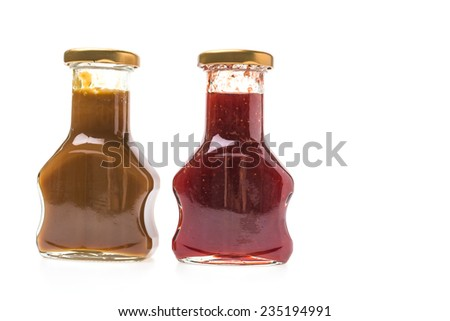 Caramel sauce and strawberry jam bottles isolated on white background