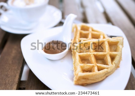 caramel sauce in white spoon and waffles with coffee , on wood