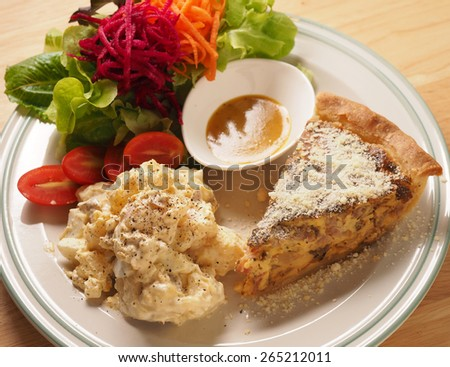 Caramelize Onion and bacon quiche served with potato salad and vegetable - stock photo