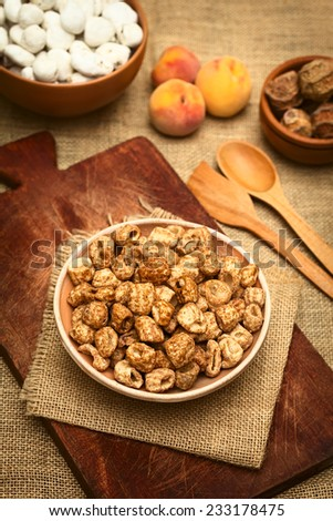 Caramelized roasted pasta, a popular Bolivian snack, served in small bowl with peach in the back, photographed  with natural light (Selective Focus, Focus on the top of the snack in the bowl) - stock photo