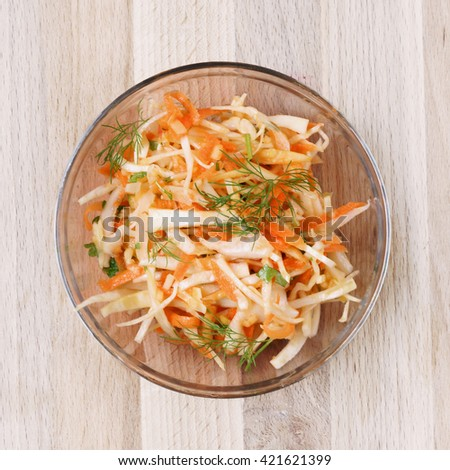 Carat and coleslaw salad in a glass bowl on rustic wooden table. Top view