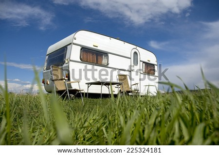 caravan camping with table and two chars - stock photo