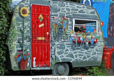 Caravan painted with flowers in a yard - stock photo