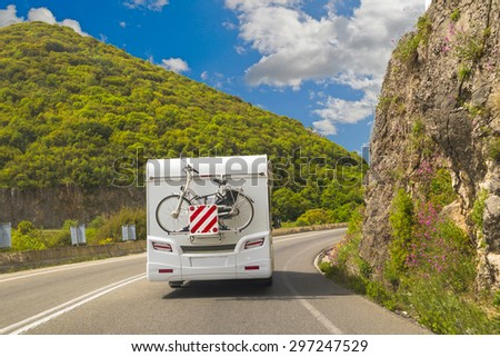 caravan road - bike, back side - green trees blue sky and clouds - stock photo