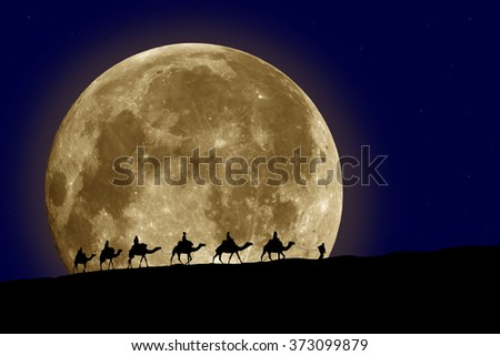 caravan silhouette on background of the moon night in the desert - stock photo