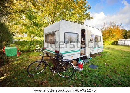 Caravan trailer and a bicycle on a green lawn under the trees, on a sunny Autumn day in France - stock photo