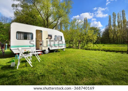 Caravan trailer on a green lawn, on a sunny spring day - stock photo