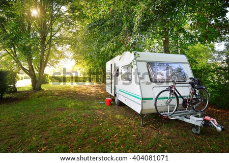 Caravan trailer on a green lawn under the trees, on a sunny summer day. Poix de Picardie, France. - stock photo