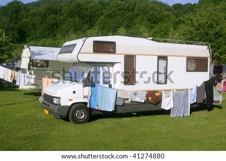 Caravan van in the green meadow forest camping - stock photo