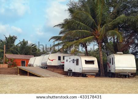 Caravans camping on beach under palm at Goa - stock photo
