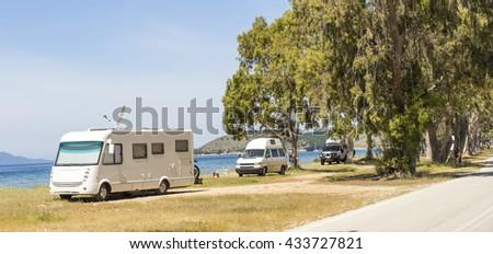 caravans cars holidays, sea trees, road - stock photo