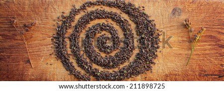 Caraway or carum carvi seeds arranged in spiral shape on old wooden cutting board. - stock photo
