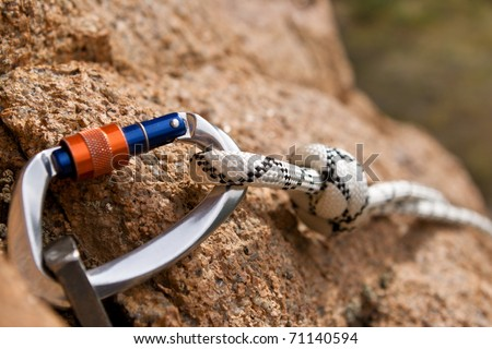 Carbine and hook with rope in stone - stock photo
