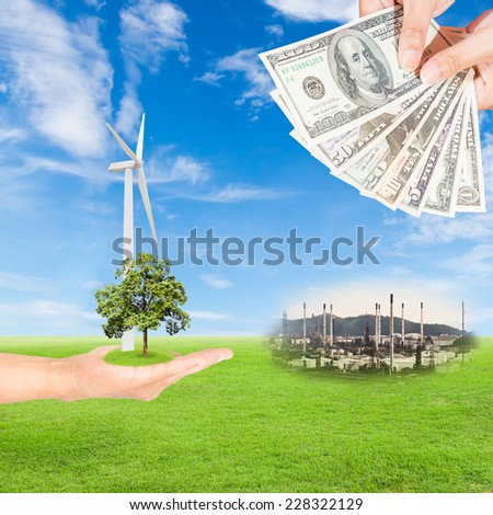 Carbon credits concept,hand holding tree and wind turbine and US Dollars banknote with oil refinery plant against green field and blue sky background - stock photo