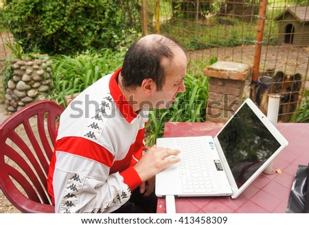 CARBONARA DI PO, ITALY - APRIL 23, 2016: Unidentified man with Kappa clothes sitting behind a Sony computer at a park on a sunny day