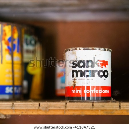 CARBONARA DI PO, ITALY - APRIL 19, 2016: Used dirty San Marco paint container on a dusty shelf - stock photo