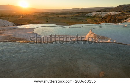 Carbonate travertines with blue water, Pamukkale, Turkey at sunset - stock photo