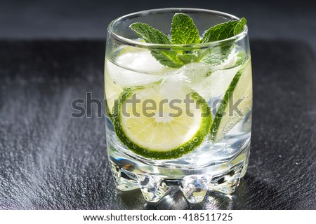 carbonated lemonade with ice in a glass, closeup - stock photo