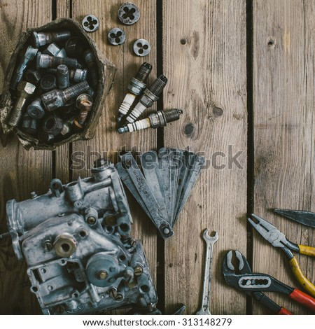 Carburetors for a car engine with tools on wooden table - stock photo