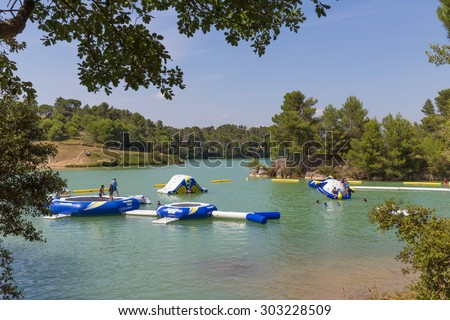 CARCASSONNE, FRANCE - JULY 26, 2014: Inflatable water playground at Lac de la Cavayere. The lake is an artificial lake close to the mediaeval town of Carcassonne. - stock photo