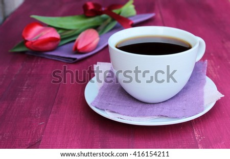 Card cup of black coffee with bouquet of fresh red tulips decorated with natural lin napkin and red satin ribbon on purple wooden background