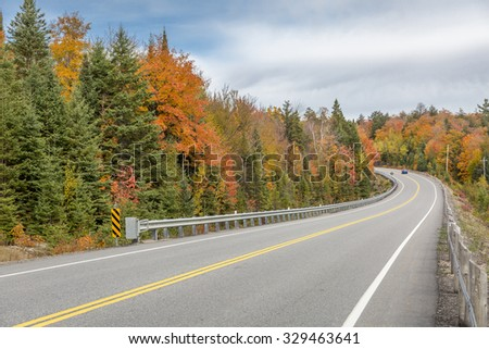 Card Driving on a Winding Road Surrounded by Fall Color - Algonquin Provincial Park, Ontario, Canada   - stock photo
