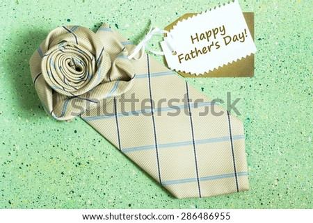 Card Father's Day - a tie in the form of roses and label with the inscription: Happy Father's Day on a green colored background - stock photo