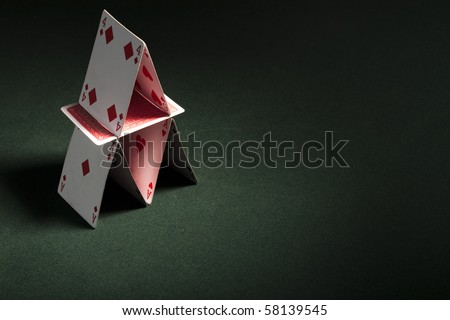 Card house made on green casino table - stock photo