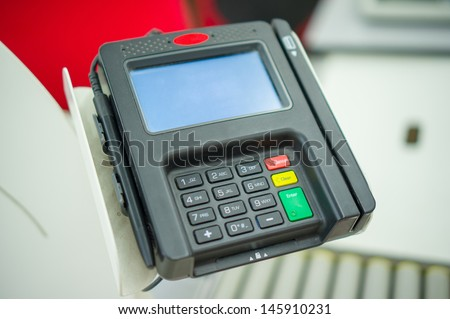 Card payment terminal at cash desk in supermarket - stock photo