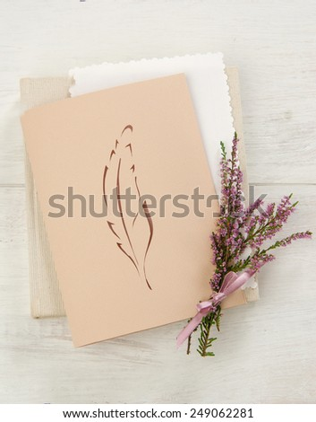 card pen technique kirigami with a bunch of flowers heather on white wooden surface - stock photo