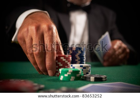card player gambling casino chips on green felt background selective focus - stock photo