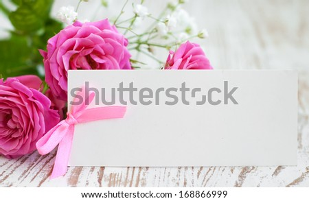 Card with a pink  roses on the wooden table