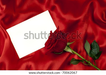 card with a red rose on red silk background - stock photo