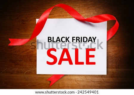 Card with Black Friday Sale text on wooden background - stock photo