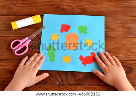 Card with bright paper sea animals and fish, glue, scissors on a brown wooden background. Kids paper project for kindergarten, elementary school, summer camp. Child put his hands on a table. Close-up  - stock photo