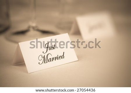 Card with inscription Just Married on table. Shallow DOF. Sepia tone. - stock photo