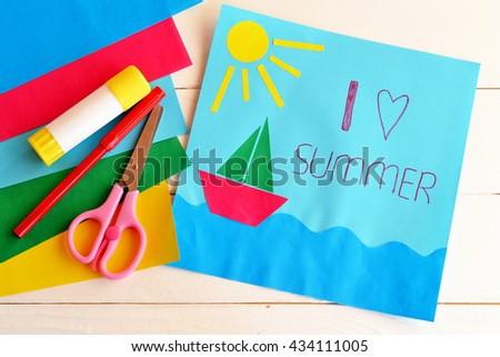 Card with text I love summer. Paper ship, sun, sea applique. Vacation pattern. Red pen, glue stick, scissors, colored paper. Fun art idea for kids. Summer vacation background. Summer vacation concept - stock photo