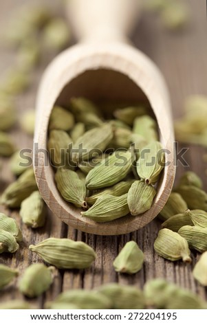 Cardamom green seeds superfood ayurveda spice in a wooden shovel on vintage background - stock photo