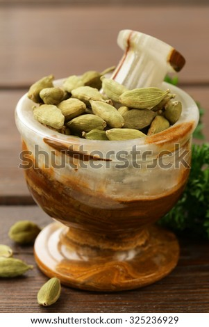 cardamom  in a stone mortar on a wooden table - stock photo