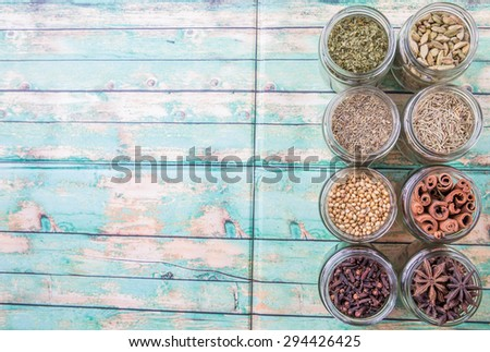 Cardamom, star anise, cinnamon, clove, coriander seed spices and parsley, thyme, rosemary herbs in mason jars over weathered wooden background - stock photo