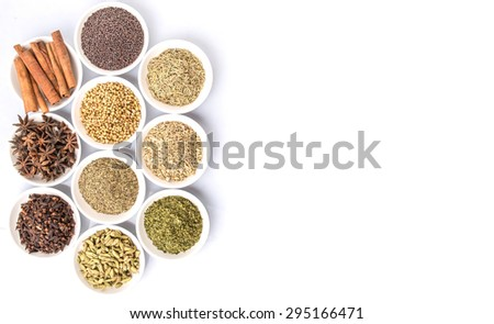 Cardamom, star anise, cinnamon, clove, coriander seed spices and parsley, thyme, rosemary herbs in white bowls over white background